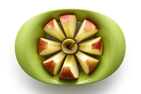 Green apple slicer with sliced apple segments from above, isolated on white.