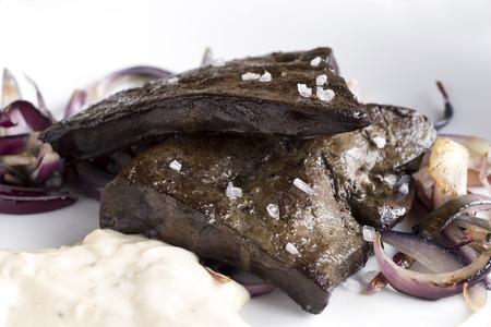 rock salt: Detail of pan fried whole pork liver with rock salt, onions and white sauce. Stock Photo