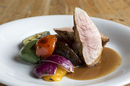 low carb diet: Gluten free chimney of Pork tenderloin steak with grilled vegetables and sauce. Wood background.