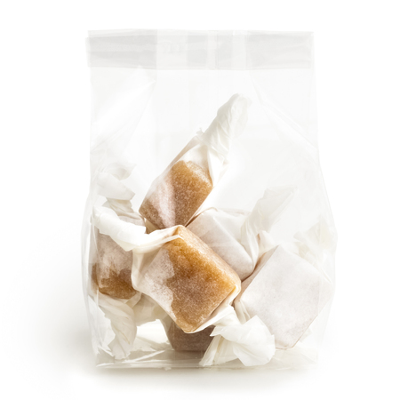 cellophane: Cellophane packet of wrapped caramel toffees isolated on white. Stock Photo