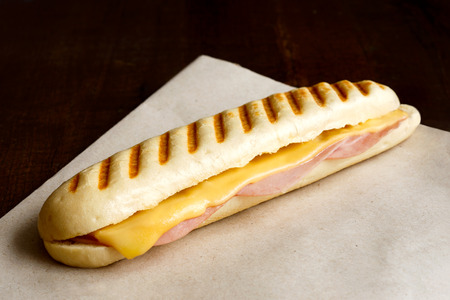 panini: Whole cheese and ham toasted panini melt. On brown paper and wood.