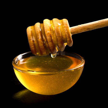 Wooden honey dipper over glass dish filled with honey. Black background.
