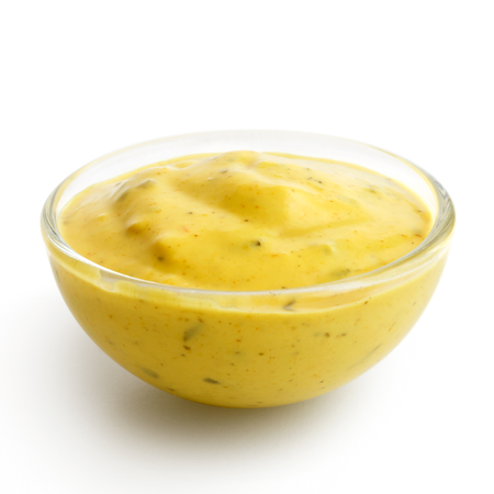 low angles: Small glass condiment bowl of  yellow curry sauce. Isolated in perspective on white.