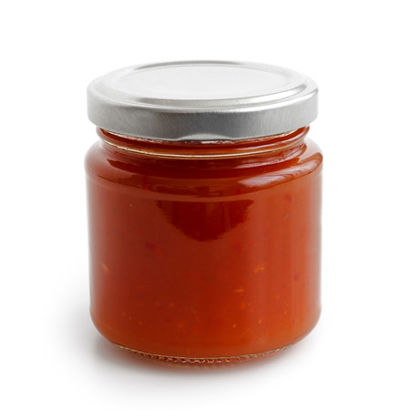 low perspective: Closed glass jar of red chilli pepper sauce. Isolated in low perspective on white. Stock Photo