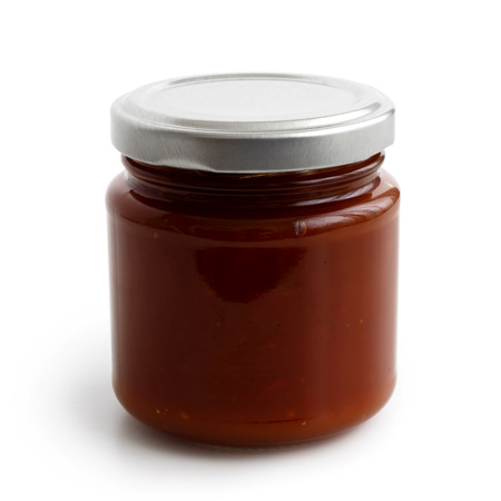 low perspective: Closed glass jar of brown tomato and red chilli pepper salsa. Isolated with low perspective.