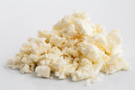 Verkruimelde witte feta kaas op een witte ondergrond.