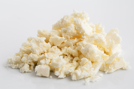 Zerbröckelt weiß Feta-Käse auf weiße Fläche isoliert.