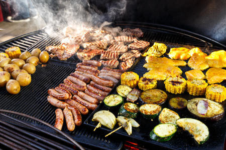 barbecue grill: Large hot smokey barbecue with meat, sausages and vegetables being cooked. Stock Photo