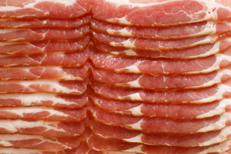 uncooked bacon: Detail of strips of streaky uncooked bacon isolated on white from above.