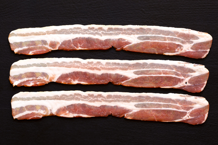 uncooked bacon: Three strips of streaky uncooked bacon isolated on black  from above.