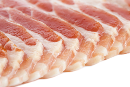 uncooked bacon: Detail of strips of streaky uncooked bacon isolated on white.