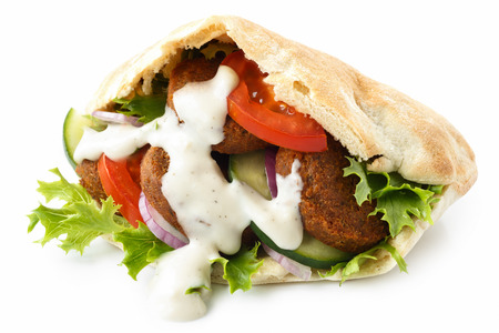 Pita bread filled with falafel, salad and white sauce isolated on white.