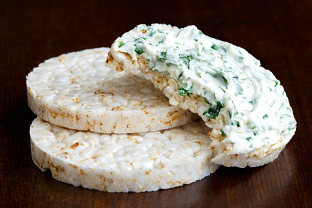 two and a half: Pile of two and half eaten puffed rice cakes isolated on dark wood. With chive and herb spread. Stock Photo