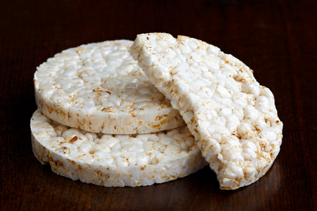 two and a half: Pile of two and half puffed rice cakes isolated on dark wood. Stock Photo