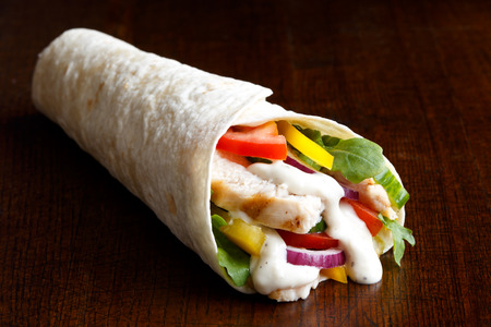 Grilled chicken and salad tortilla wrap with white sauce isolated on dark background.