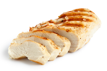 Partially sliced grilled chicken breast with black pepper and rock salt isolated on white.