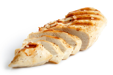 Partially sliced grilled chicken with black pepper and rock salt isolated on white.