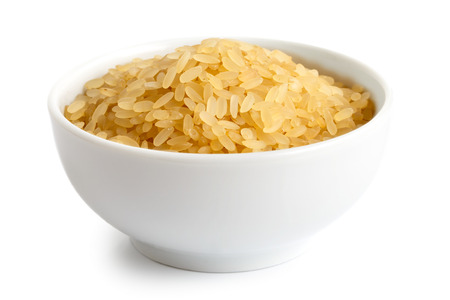 processed grains: Bowl of short grain parboiled rice isolated on white. Stock Photo