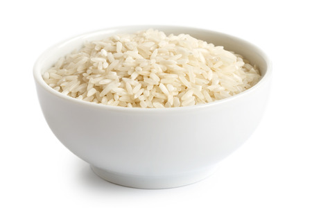 processed grains: Bowl of long grain white rice isolated on white.