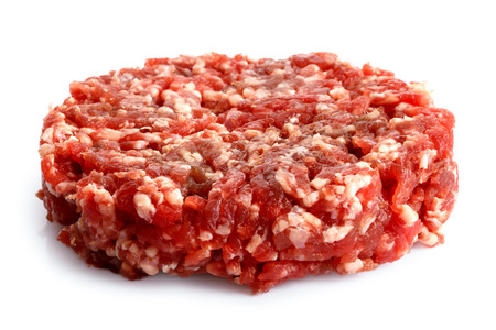 Single raw hamburger patty isolated on white. Stock Photo