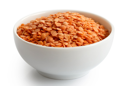 seed pots: Dry red lentils in white ceramic bowl isolated on white.