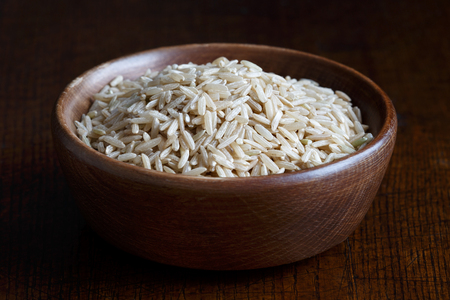 seed pots: Dry long grain brown rice in brown wooden bowl isolated on dark wood.