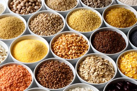 Fond de nombreux grains et légumineuses dans des plats en céramique blanche.