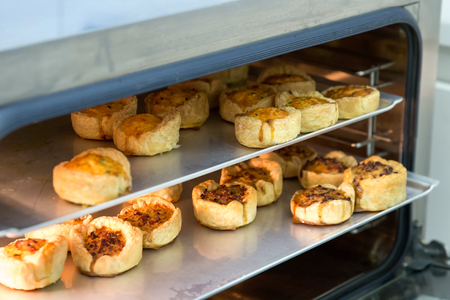 mini oven: Cheese and bacon mini quiches on baking trays in commercial oven.