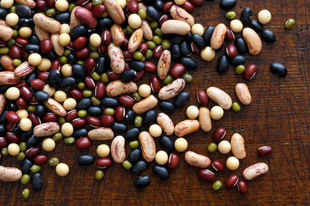Mixed dry beans on dark wood from above. Фото со стока