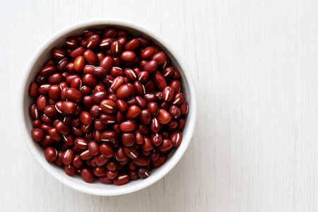 Dry adzuki beans  in white ceramic bowl isolated on painted white wood from above. Stock Photo