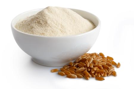 White flour in white ceramic bowl isolated on white. Next to kamut wheat kernels.