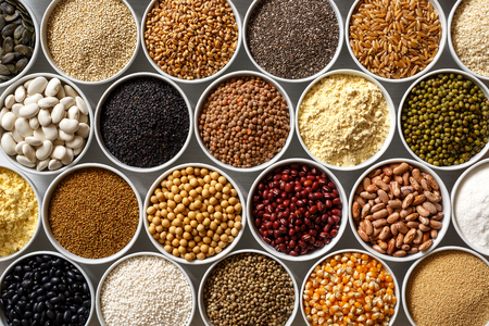 Arranged white bowls with uncooked pulses, grains and seeds on white wood from above. Stockfoto
