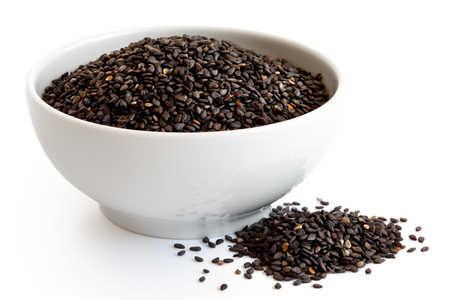 Black sesame seeds  in white ceramic bowl isolated on white. Spilled seeds. Standard-Bild