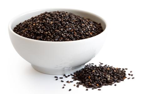 Zwarte sesamzaden in witte ceramische die kom op wit wordt geïsoleerd. Gemorste zaden. Stockfoto - 82316461