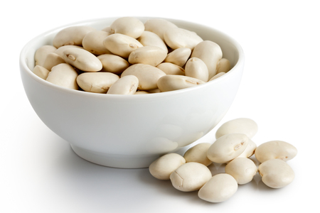 Dry butter beans  in white ceramic bowl isolated on white. Spilled beans.
