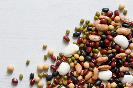 Mixed dry beans on white wooden board from above. Space for text. Stock fotó