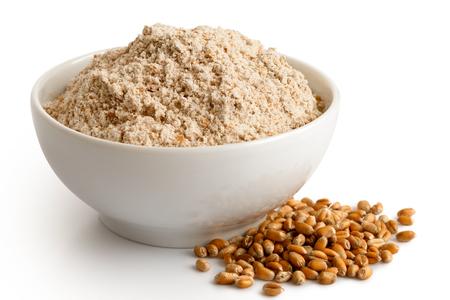 Spelt whole grain flour in white ceramic bowl isolated on white. Spilled winter wheat kernels. Standard-Bild