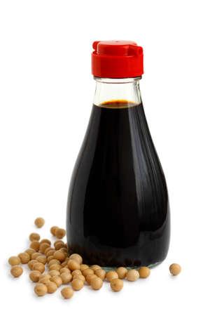Bouteille en verre de sauce soja avec couvercle en plastique rouge isolé sur blanc. Haricots de soja déversés.