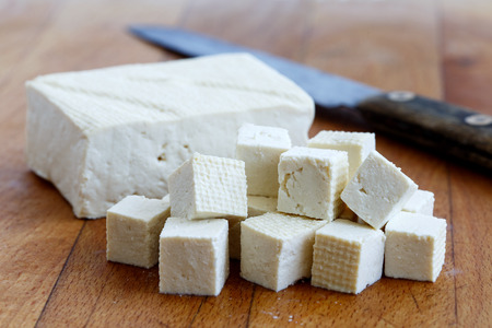 Single block of white tofu with cut tofu cubes and rustic knife on wooden chopping board.