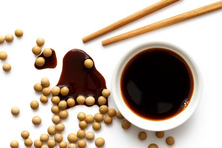 Sauce soja dans un bol en céramique blanc sur blanc avec des baguettes en bois. Sauce de soja renversée et fèves de soja.