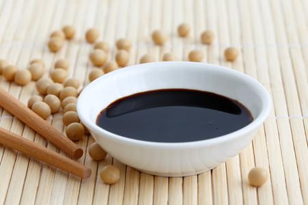 Sauce soja dans un bol blanc sur une natte de bambou avec des baguettes et des fèves de soja renversées.