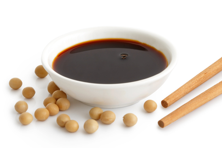 sauce soja dans un bol blanc sur blanc avec des baguettes et des graines de soja bouillies