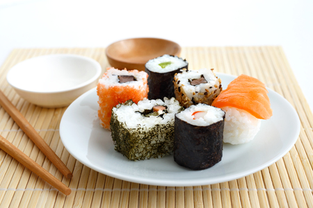 Selection of sushi on bamboo mat with chopsticks. Stock Photo