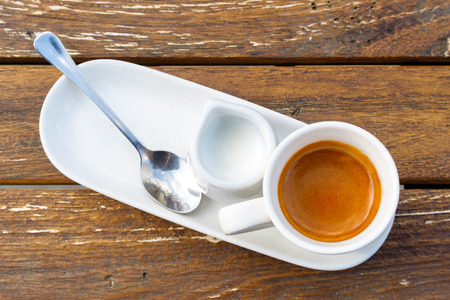 Espresso in white ceramic cup next to milk and spoon on rustic wooden table from above.