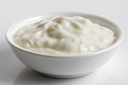 White ceramic bowl of skyr yoghurt isolated on grey background.