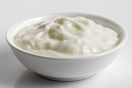 White ceramic bowl of skyr yoghurt isolated on grey background.