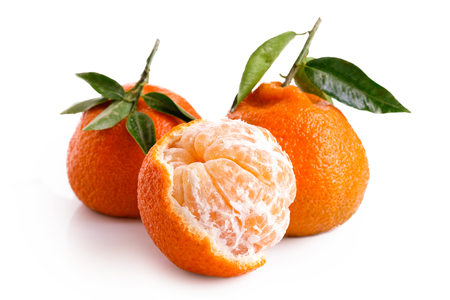 One half peeled and two whole mandarins with leaves isolated on white. Stock Photo