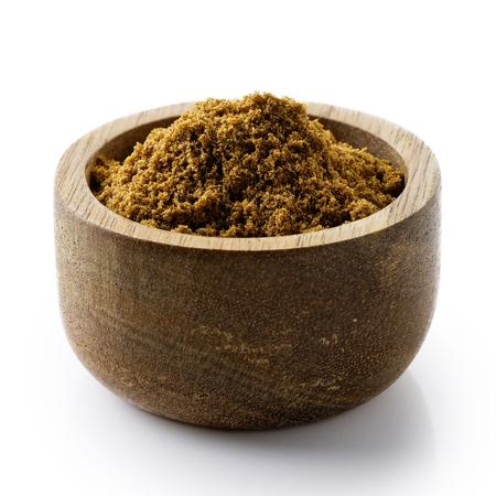 Ground cumin in dark wood bowl isolated on white. 스톡 콘텐츠