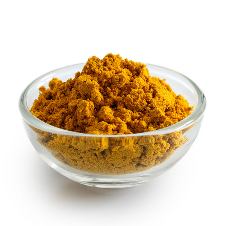 Curry powder in glass bowl isolated on white.