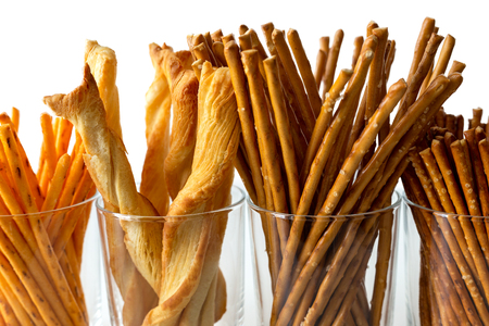 Selection of grissini, pretzels and cheese sticks in glasses on white background.